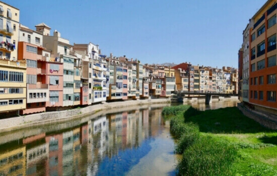 The Onyar river in Girona with the reflection in the sun of the water.